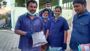 Workers of Division 19 at the Arulanandam Nagar Burial Ground happily display packets of compost produced at the facility. Pic: Aarti Madhusudan
